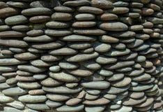 Αμμοχάλικο χαλικιών ποταμών γύρω από τον τοίχο πετρών που διαμορφώνεται για το υπόβαθρο στοκ φωτογραφίες