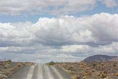 Αμμοχάλικο/βρώμικος δρόμος και παχιά σύννεφα στοκ φωτογραφία