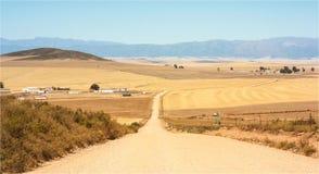 Αμμοχάλικο/βρώμικος δρόμος στα καλλιεργήσιμα εδάφη στοκ εικόνα