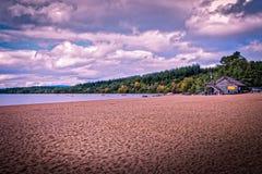Αμμώδης ακτή αμμοχάλικου Morlich λιμνών, Aviemore, κοντά στον καφέ boathouse μια νεφελώδη ημέρα με τα πράσινα δέντρα στο υπόβαθρο στοκ φωτογραφία με δικαίωμα ελεύθερης χρήσης