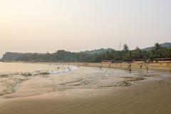 Αμμώδης παραλία θάλασσας ενάντια στο σκηνικό της κολύμβησης ανθρώπων και η πράσινη ζούγκλα το βράδυ στοκ εικόνα