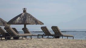 Αμμώδης παραλία με τα σαλόνια μονίππων και sunshades στο τροπικό θέρετρο πρεσών Ινδονησία απόθεμα βίντεο