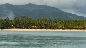 Αμμώδης παραλία με τις μικρές παραδοσιακές ταϊλανδικές καλύβες ύφους και τον ήρεμο ωκεανό, Koh νησί Samui, Ταϊλάνδη Πράσινοι φοίν φιλμ μικρού μήκους