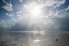 Αμμώδης παραλία με το σαφές νερό και όμορφος μπλε ουρανός με τα σύννεφα Στοκ Φωτογραφίες