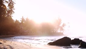 Αμμώδης παραλία στα αφρίζοντας ωκεάνια κύματα που απεικονίζουν το φως του ήλιου απόθεμα βίντεο