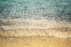 Αμμώδης παραλία και διαφανή κύματα θάλασσας, χαλίκια κάτω από το νερό Στοκ Φωτογραφία