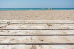 Αμμώδης παραλία την ηλιόλουστη ημέρα με την ξύλινη διάβαση πεζών Στοκ Φωτογραφία
