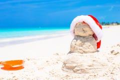 Αμμώδης χιονάνθρωπος με το κόκκινο καπέλο Santa στο λευκό Στοκ φωτογραφία με δικαίωμα ελεύθερης χρήσης