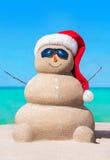 Αμμώδης χιονάνθρωπος στο καπέλο Χριστουγέννων και γυαλιά ηλίου στην τροπική παραλία Στοκ Εικόνες