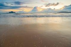Αμμώδη παραλία και κύματα ενάντια στον ήλιο ρύθμισης Στοκ Φωτογραφίες