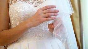 Αμοιβές νυφών η κινηματογράφηση σε πρώτο πλάνο, χέρια της νύφης με ένα ευγενές μανικιούρ κρατά ένα λευκό σαν το χιόνι πέπλο, στα  απόθεμα βίντεο