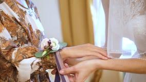 Αμοιβές νυφών Προετοιμασία για τη γαμήλια τελετή η κινηματογράφηση σε πρώτο πλάνο, θηλυκά χέρια, η νύφη δένει μια μπουτονιέρα λου απόθεμα βίντεο