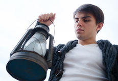 λαμπτήρας κηροζίνης περιστασιακά ακόμα χρησιμοποιούμενος ένας νεαρός άνδρας με στο χέρι του ενάντια στον ουρανό Στοκ Εικόνες