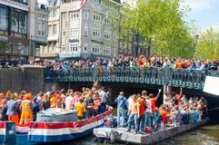 ΑΜΣΤΕΡΝΤΑΜ, ΚΑΤΩ ΧΏΡΕΣ 27 ΑΠΡΙΛΊΟΥ: Βάρκα κόμματος με το πλήθος των ανθρώπων στη γέφυρα την ημέρα τον Απρίλιο 27.2015 του βασιλιά Στοκ Εικόνα
