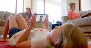 Αμφιθαλείς που χρησιμοποιούν την ψηφιακά ταμπλέτα και το lap-top στο καθιστικό 4k απόθεμα βίντεο