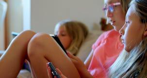 Αμφιθαλείς που χρησιμοποιούν το κινητό τηλέφωνο και την ψηφιακή ταμπλέτα στο καθιστικό 4k φιλμ μικρού μήκους