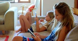 Αμφιθαλείς που χρησιμοποιούν το κινητό τηλέφωνο και την ψηφιακή ταμπλέτα στο καθιστικό 4k απόθεμα βίντεο
