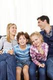 Αμφιθαλείς που κρατούν τους αντίχειρες επάνω μεταξύ των γονέων Στοκ Εικόνες