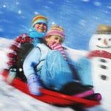 Αμφιθαλείς που παίζουν το έλκηθρο χιονιού στην έννοια χιονιού Στοκ Φωτογραφίες