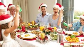 Αμφιθαλείς που τραβούν μια κροτίδα Χριστουγέννων στον πίνακα γευμάτων απόθεμα βίντεο