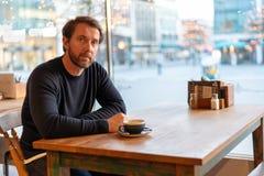 Αμφισβητήσιμη μέση ηλικίας καυκάσια αρσενική συνεδρίαση στον πίνακα στη καφετερία στοκ φωτογραφία με δικαίωμα ελεύθερης χρήσης