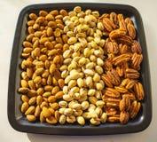 Αμύγδαλα, φυστίκια και πεκάν καρυδιών στο μαύρο πιάτο, κινηματογράφηση σε πρώτο πλάνο, σύνολο Στοκ φωτογραφία με δικαίωμα ελεύθερης χρήσης
