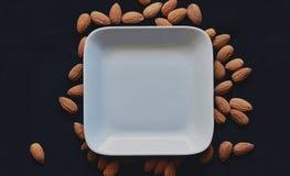 Αμύγδαλα έξω από το άσπρο πιάτο στο μαύρο κλίμα στοκ εικόνες με δικαίωμα ελεύθερης χρήσης