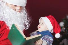 Ανάγνωση Άγιου Βασίλη για το βιβλίο μωρών με το παραμύθι Χριστουγέννων Στοκ Φωτογραφία