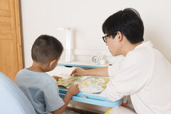 Ανάγνωση αγοριών μεγαλοφώνως με τη διδασκαλία στοκ εικόνα