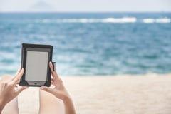 Ανάγνωση από τον ε-αναγνώστη στην παραλία Στοκ Φωτογραφία