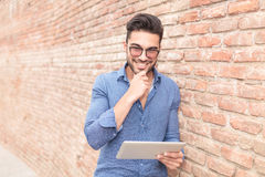 Ανάγνωση ατόμων χαμόγελου σκεπτική σε έναν υπολογιστή ταμπλετών Στοκ εικόνες με δικαίωμα ελεύθερης χρήσης