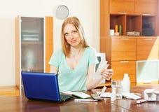 Ανάγνωση γυναικών για τα φάρμακα στο lap-top Στοκ Φωτογραφίες