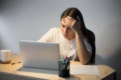 Ανάγνωση γυναικών για το πρόβλημα στο φορητό προσωπικό υπολογιστή αργά τη νύχτα στοκ εικόνα