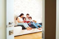 Ανάγνωση ενός βιβλίου με την οικογένειά σας οικογένεια ευτυχής Δίδυμα παιδιών Στοκ Εικόνες