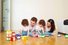 Ανάγνωση ενός βιβλίου με την οικογένειά σας οικογένεια ευτυχής Δίδυμα παιδιών Στοκ εικόνα με δικαίωμα ελεύθερης χρήσης