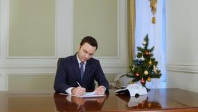 Ανάγνωση επιχειρηματιών και υπογραφή των εγγράφων που κάθονται από δέντρο επιτραπέζιου το στην αρχή κοντινό νέο έτους στοκ εικόνες με δικαίωμα ελεύθερης χρήσης