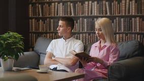 Ανάγνωση ζεύγους eBook και φυσικό βιβλίο τυπωμένων υλών στον καφέ φιλμ μικρού μήκους