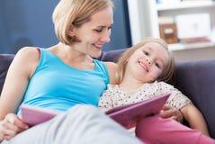 Ανάγνωση μητέρων και κορών στον καναπέ στοκ φωτογραφία με δικαίωμα ελεύθερης χρήσης