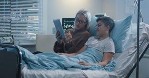 Ανάγνωση μητέρων μεγαλοφώνως στον άρρωστο γιο στοκ φωτογραφίες με δικαίωμα ελεύθερης χρήσης