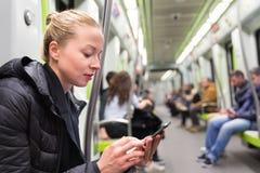 Ανάγνωση νέων κοριτσιών από την κινητή τηλεφωνική οθόνη στο μετρό Στοκ Εικόνα