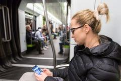 Ανάγνωση νέων κοριτσιών από την κινητή τηλεφωνική οθόνη στο μετρό Στοκ εικόνα με δικαίωμα ελεύθερης χρήσης