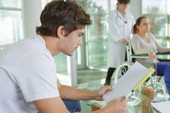 Ανάγνωση νεαρών άνδρων περιμένοντας στο νοσοκομείο loob Στοκ Εικόνες