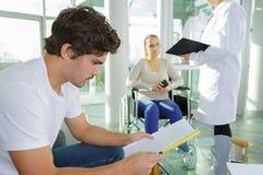 Ανάγνωση νεαρών άνδρων περιμένοντας τη στροφή Στοκ Εικόνα