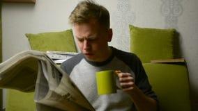 Ανάγνωση της παλαιάς εφημερίδας πίνοντας την κινηματογράφηση σε πρώτο πλάνο πορτρέτου τσαγιού, πράσινος καναπές έννοιας απόθεμα βίντεο