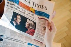 Ανάγνωση Financial Times γυναικών με το Emmanuel Macron και το θαλάσσιο Λ Στοκ φωτογραφίες με δικαίωμα ελεύθερης χρήσης