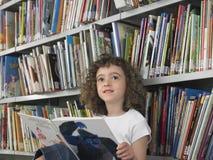 Ανάγνωση Storybook κοριτσιών στη βιβλιοθήκη Στοκ Φωτογραφίες