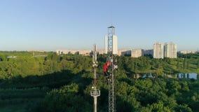 Ανάδοχος που εργάζεται στον ιστό τηλεπικοινωνιών στο ύψος στο υπόβαθρο του όμορφου τοπίου πόλεων, άποψη κηφήνων φιλμ μικρού μήκους