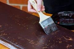 Ανάδοχος που χρωματίζει ένα ξύλινο baseboard για την ανακαίνιση στοκ φωτογραφία