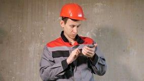 Ανάδοχος hardhat που χρησιμοποιεί το τηλέφωνο στην περιοχή απόθεμα βίντεο