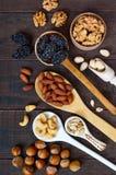 Ανάμεικτα διαφορετικά καρύδια, δαμάσκηνα, σπόροι κολοκύθας στα κουτάλια σε ένα σκοτεινό ξύλινο υπόβαθρο Στοκ Εικόνα